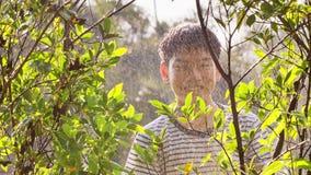 4K handbediend van Aziatische jongen op een zonnige hete dag, speelt een jongen met water en geniet van het die zeer met water ba stock video