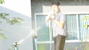 4K handbediend van Aziatische jongen op een zonnige hete dag, speelt een jongen met water en geniet van het die zeer met water ba stock videobeelden