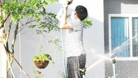 4K Handheld азиатского мальчика на солнечный горячий день, мальчик играет с водой и наслаждается им очень купая с водой акции видеоматериалы