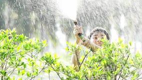 4K Handheld азиатского мальчика на солнечный горячий день, мальчик играет с водой и наслаждается им очень купая с водой видеоматериал