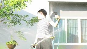 4K Handheld азиатского мальчика на солнечный горячий день, мальчик играет с водой и наслаждается им очень купая с водой сток-видео