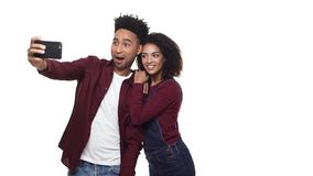 4k - Happy cheerful afro american couple making a selfie and watching made photos isolated over white background.  stock video footage