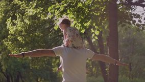 4K Happy father whirls his smiling child on neck in the park stock footage
