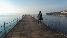 4K. Happy girl rides a bicycle over the blue sea on the pier at sunny day. Vacation time stock footage