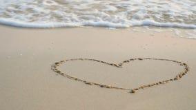 4K Herzzeichnung auf Sandstrand mit weicher Welle des blauen Meeres, Kräuselungsmeereswoge mit weißem Blasenschaum stock footage
