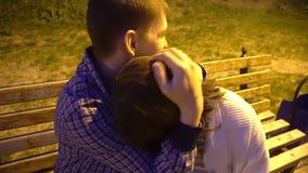 4k het aantrekkelijke jonge paar in liefde bij de omhelzing van de parkbank, knuffel, omhelst Gelukkig, in liefde, mannetje en wi stock videobeelden