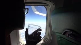 4K het Aziatische Jonge mooie meisje kijkt uit vliegtuigvenster en drinkwater stock videobeelden