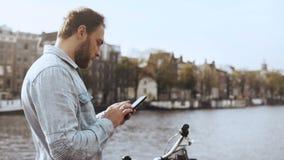 4K het Europese zakenman texting op een rivierbrug Volwassen gebaard mannetje met fiets in blauw overhemd die in mobiel bureau we stock footage