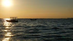 4K het silhouet van kleine boot over het overzees met kleine golf in zonsondergang of zonsopgangtijd, mooi zonlicht denkt met wat stock videobeelden