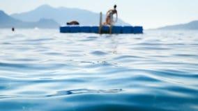 4k hors de la vidéo de foyer des personnes heureuses détendant sur flotter le ponton en plastique à la mer clips vidéos