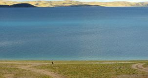 4k huge clouds rolling over lake namtso,Tibetans walking on the lakeside. stock video footage