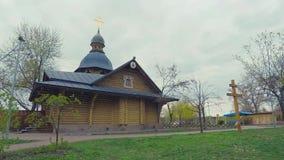 4K Hyperlaps Träkyrkan i den gamla ryska stilen med ett guld- kors i parkerar av staden av Kiev arkivfilmer