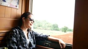 4K i bei sunglass asiatici di usura di donna ed ascoltano musica dal trasduttore auricolare che guarda da una finestra del treno  archivi video