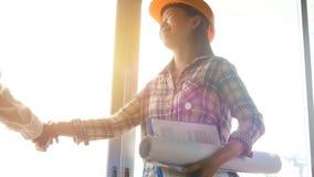 4K ingegnere asiatico felice della donna come i muratori con il modello e contratto a disposizione con il casco giallo protettivo video d archivio