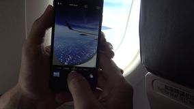4k Interior airplane, passenger on a plane using Smartphone take picture stock video footage