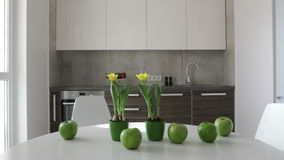 4K. Interior of modern kitchen in scandinavian style. Motion panoramic view with apples and flowers stock video