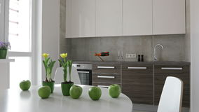 4K. Interior of modern kitchen in scandinavian style. Motion panoramic view with apples and flowers stock video footage