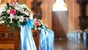 4K. interior view of empty church with wooden bench decorated with flower bouquet and blue ribbon blown by the wind. Sunlight through church stained glass stock footage