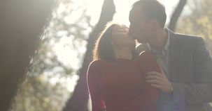 4K Jesień klimaty Obsługuje uściśnięcie kobiety ofertę od za i buziaki jej pozycja w jesień parku z złotymi liśćmi zbiory