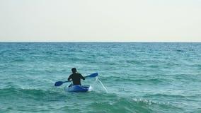 4K jeune homme actif de sport s'asseyant dans le bateau de kayak et barbotant au-dessus de la mer, activité de sports d'été banque de vidéos