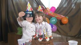 4k - Jeunes belles filles jumelles prenant un selfie (autoportrait) avec un smartphone à une fête d'anniversaire banque de vidéos