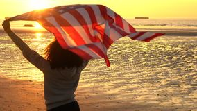 Girl teenager female young woman holding an American US Stars and Stripes flag on a beach at sunset or sunrise. 4K jib crane video clip of mixed race African stock video