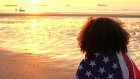 Girl teenager female young woman wrapped in an American US Stars and Stripes flag on a beach at sunset or sunrise. 4K jib crane video clip of mixed race African stock footage