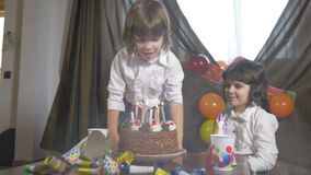 4k - Jonge mooie meisjes blazende kaarsen op een verjaardagscake met haar tweelingzuster stock footage