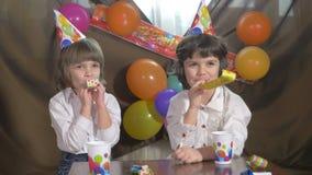 4k - Jonge mooie tweelingmeisjes die partijhoornen blazen stock footage