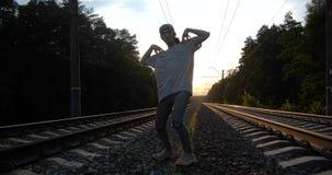 4k - Jovem morena carismática dançando krump entre a trilha ferroviária no pôr do sol, em câmera lenta video estoque