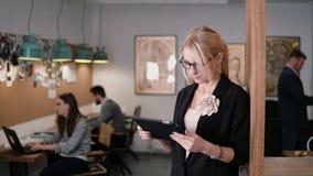 4K junge schöne blonde Geschäftsfrau benutzt eine Tablette des Bildschirm- im modernen Startbüro Lizenzfreie Stockbilder