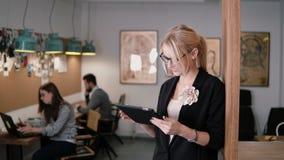 4K junge schöne blonde Geschäftsfrau benutzt eine Tablette des Bildschirm- im modernen Startbüro Stockbild