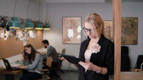 4K junge schöne blonde Geschäftsfrau benutzt eine Tablette des Bildschirm- im modernen Startbüro Stockfoto