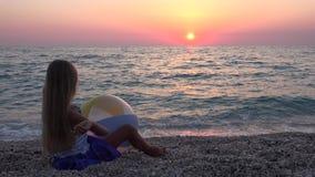4K kind het Spelen op Strand in Zonsondergang, Gelukkig Meisje die Kiezelstenen in Zeewater werpen stock videobeelden