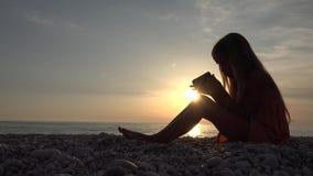 4K kind het spelen smartphone op strand, zonsondergangoverzees, meisjessilhouet op kustlijn stock video