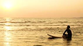 4K konturn av surfaremannen kopplar av, genom att sitta på surfingbrädan över havet på solnedgången på den tropiska stranden Spor stock video