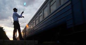 4k - l'artista al tramonto fa il trucco del pericolo sulla ferrovia vicino al treno del movimento video d archivio