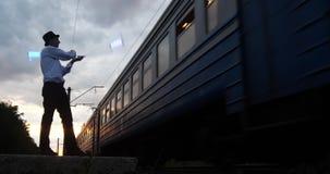 4k - l'artista al tramonto fa il trucco del pericolo sulla ferrovia vicino al treno del movimento stock footage