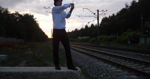 4k - l'artista al tramonto fa il trucco del pericolo sulla ferrovia vicino al treno del movimento archivi video