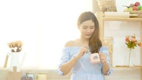 4K la belle femme asiatique ont plaisir à boire du café pendant le matin avec le visage souriant près de la fenêtre avec la lumiè banque de vidéos