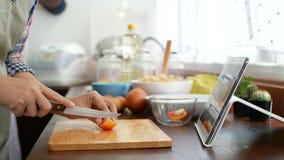 4K la diapositiva del finger del uso de la mujer en la pantalla de la tableta, cortando el tomate rojo prepara los ingredientes p