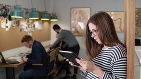 4K la giovane donna di affari castana attraente del primo piano utilizza una compressa dello schermo attivabile al tatto nell'uff Immagini Stock