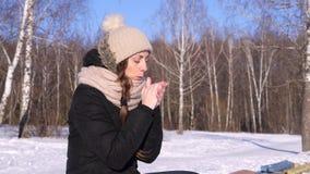 4K, la mujer en sombrero y la chaqueta negra en el invierno estornuda cerca de un bosque almacen de metraje de vídeo