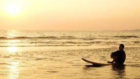 4K la silhouette de l'homme de surfer détendent en se reposant sur la planche de surf au-dessus de la mer au coucher du soleil su banque de vidéos