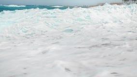 4k langzame geanimeerde video van krachtige turkooise overzeese golven die op oever bij heldere zonnige dag breken stock videobeelden