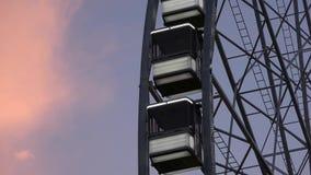 4K Las cabinas de una noria que esta parada está colgando Es puesta del sol metrajes