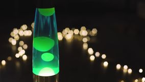 4k lava lamp retro vintage hippie abstract background, green wax moving floating. Bokeh of the garlands in background