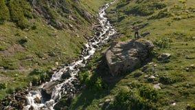 4k - Le type prend une fille sur la vallée avec une rivière de montagne, action aérienne banque de vidéos