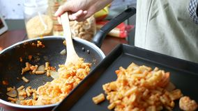 4k lengte de vrouwenhand neemt de macaronilepel van de pan in de schotel en dient na afwerking het koken stock footage