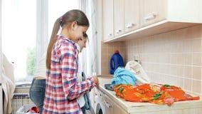 4k lengte die van leuk meisje haar moeder helpen die en kleren sorteren vouwen bij wasserij stock footage